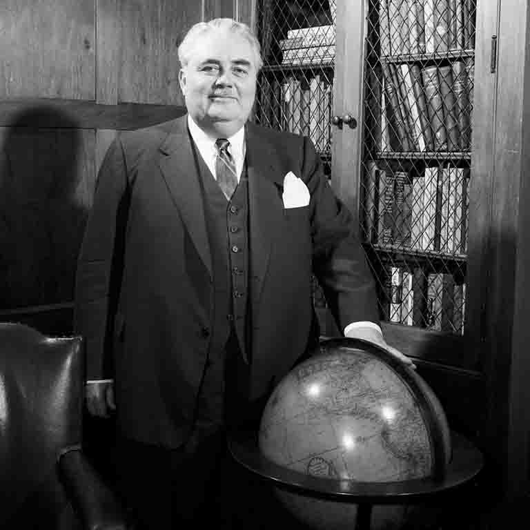 Former Indiana University President Herman B Wells stands beside a globe.