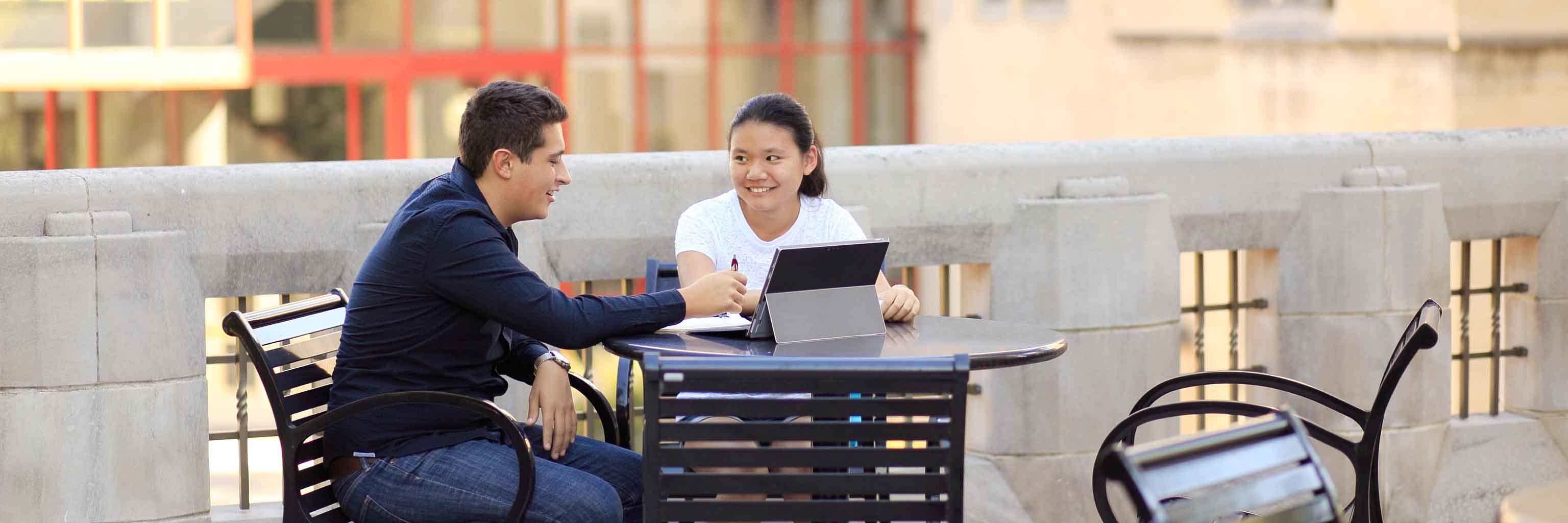 Two students talk at an outdoor table.