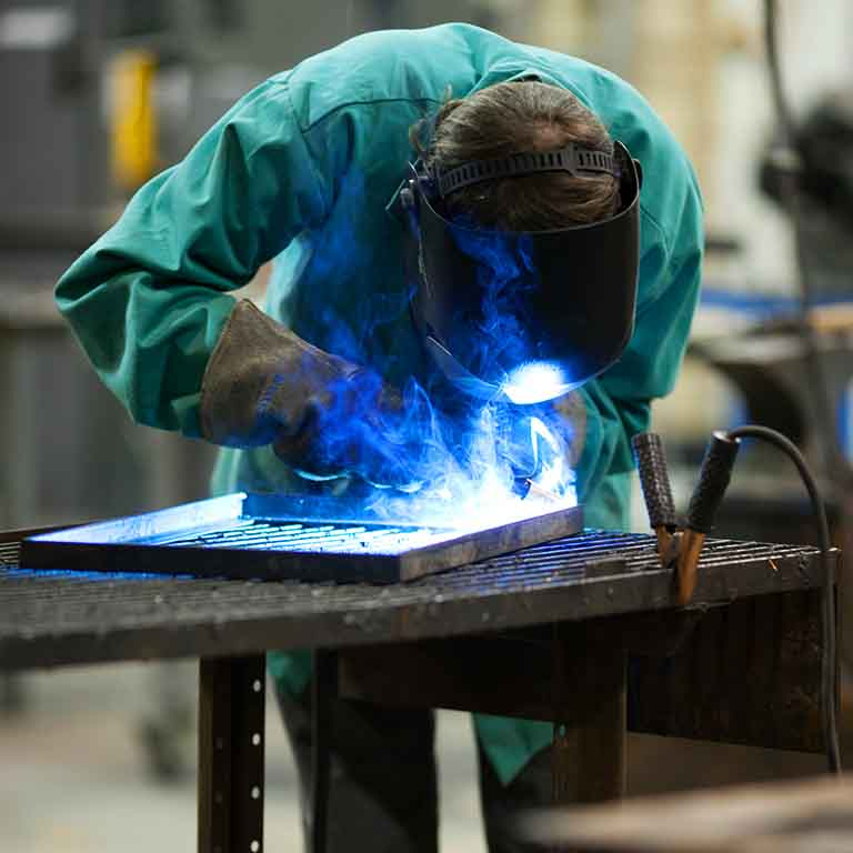 A student welds something in the metal shop.
