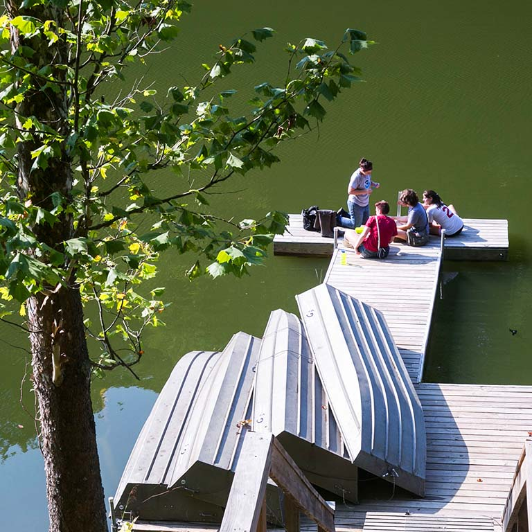 Students sit on a dock in IU's research and teaching preserve.