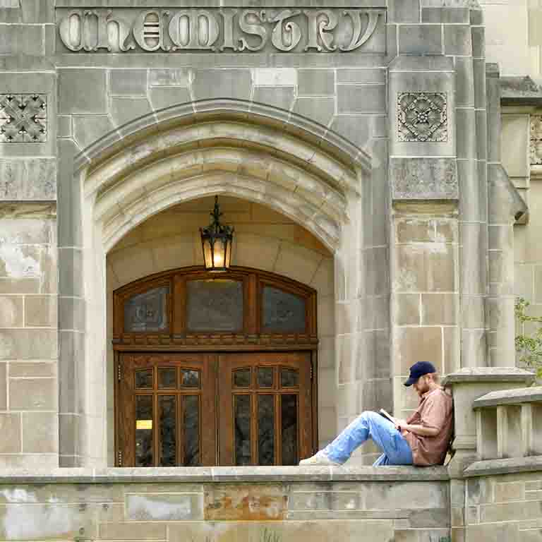 A student sits on a limestone ledge outside the Chemistry Building and reads.