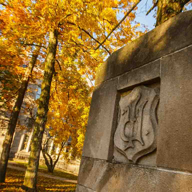 An IU emblem on a stone structure, beside trees with orange and yellow leaves in autumn