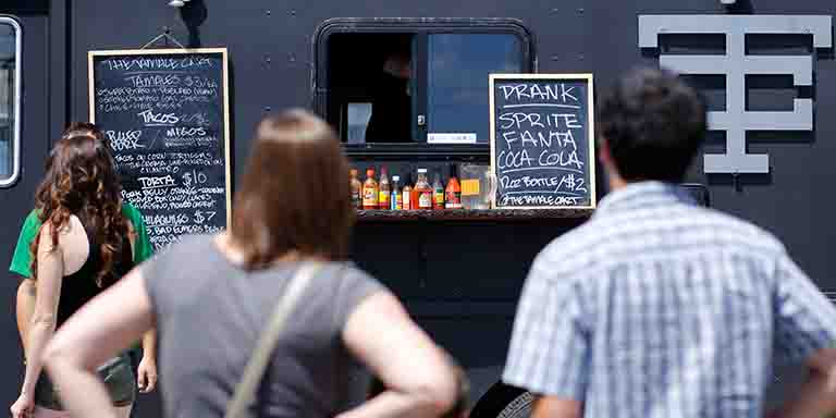 People look at the menus at a food truck.