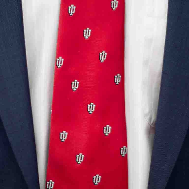 A close-up of a red tie with the IU logo printed in white.