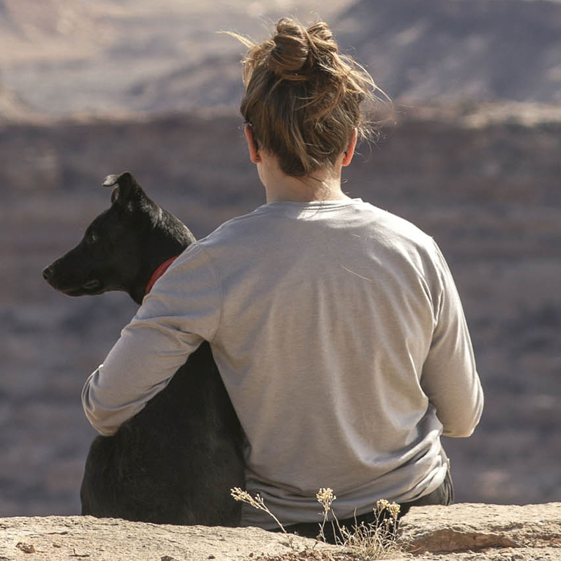 girl and dog sitting looking over a mountain range