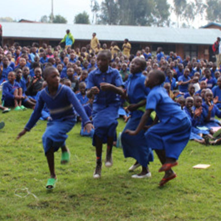 Children dressed in blue dancing in front of peers at school assembly