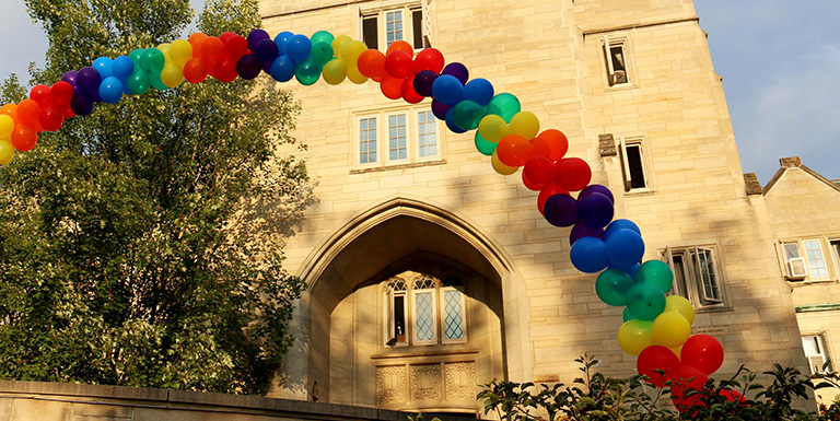 Image of the Collins Living-Learning Center entrance, where a balloon rainbow can be seen.