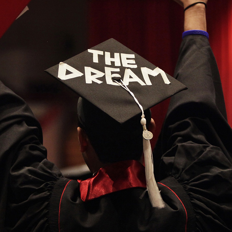"Graduate wearing cap that reads, ""The Dream."""