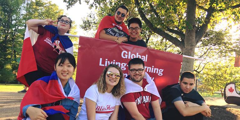 Members of the Global Learning-Living Center pose for a photo at the Homecoming Parade.