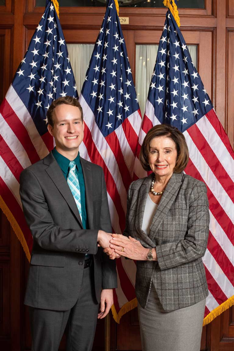 James Basset and Nancy Pelosi in front of American flag