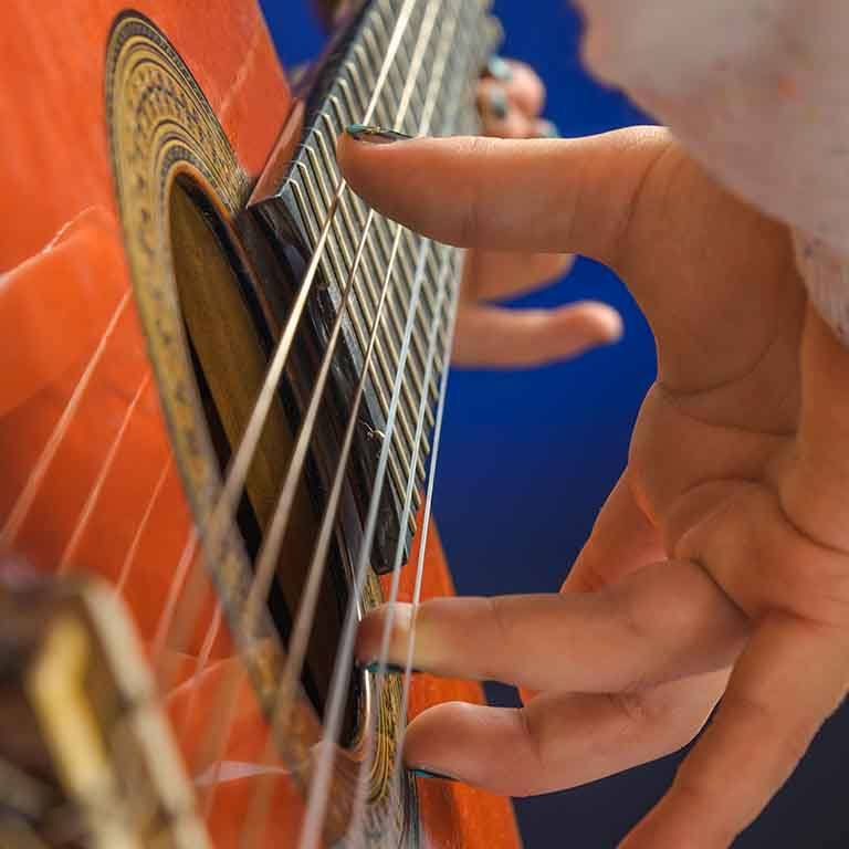 A closeup of a hand playing a guitar