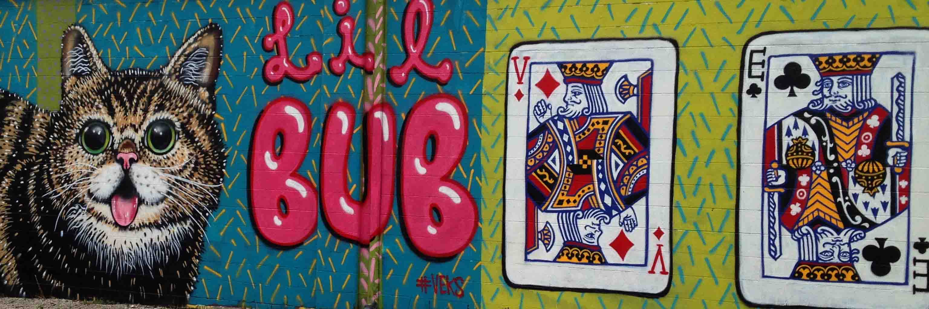 A mural depicting Lil Bub the cat and two playing cards.