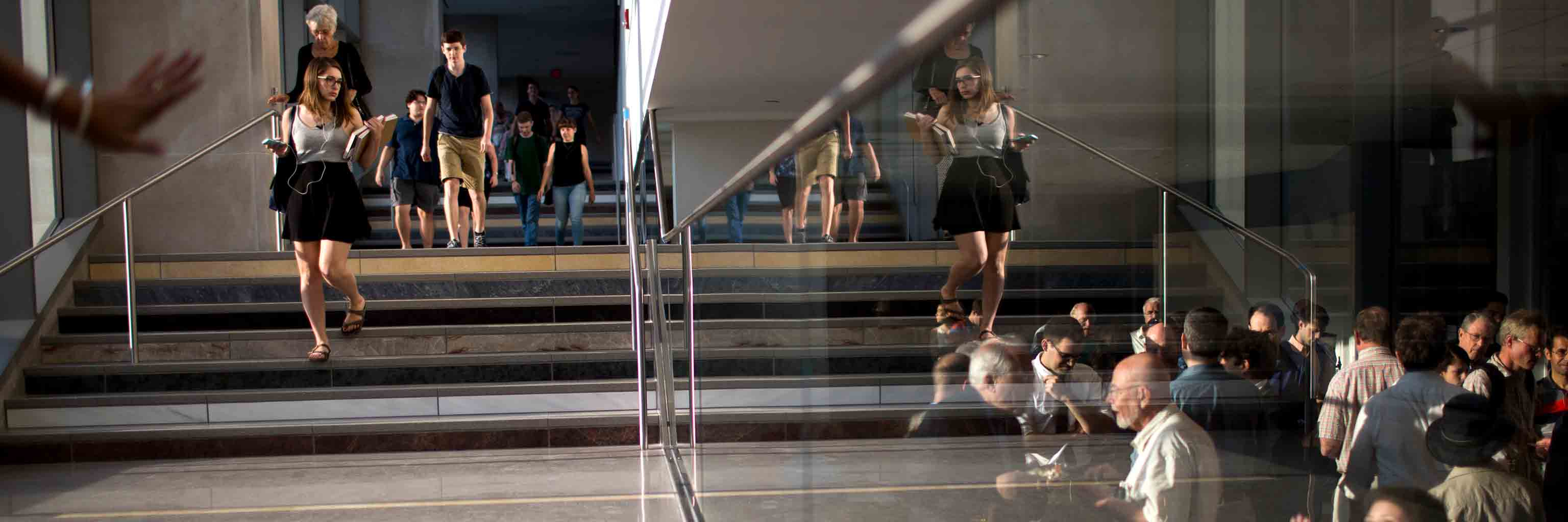 People, reflected in glass, walk down stairs.