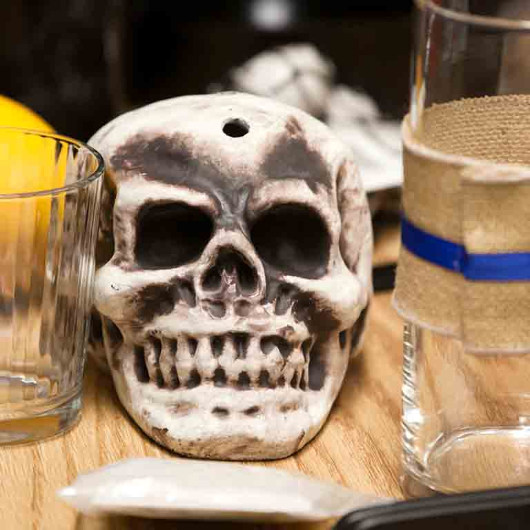 A Day of the Dead skull rests on a table between two glasses.