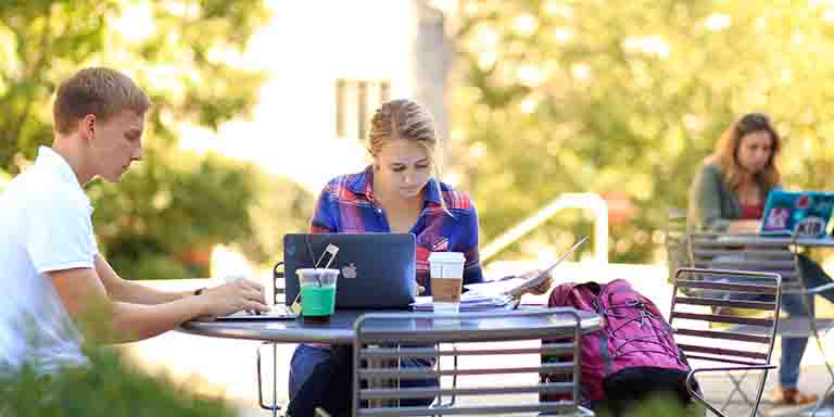 Students drink coffee as they study at an outdoor table.
