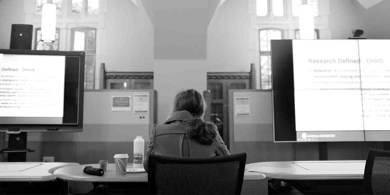 A student sits in front of large computer screens in an older building.